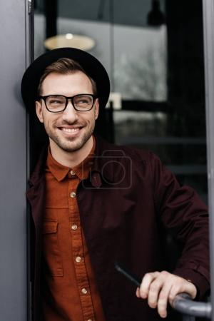 cheerful stylish man in eyeglasses and trendy hat