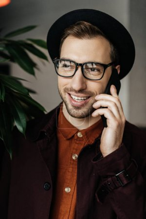 handsome cheerful man in eyeglasses and hat talking on smartphone