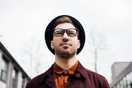 Photo pour Vue de dessous du bel homme à la mode dans les lunettes et chapeau - image libre de droit