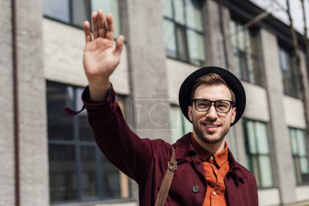 stylish young man in glasses and hat waving to someone