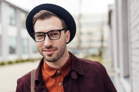 handsome smiling young man in trendy hat and eyeglasses