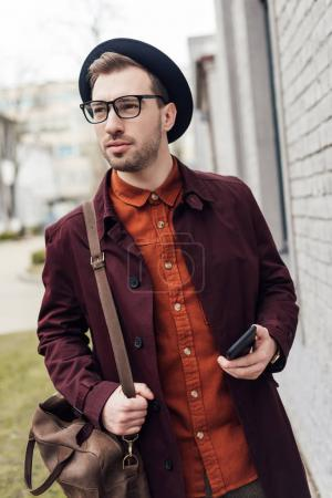 handsome elegant man in hat and glasses with bag holding smartphone