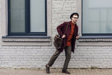 stylish man with bag and smartphone running on street