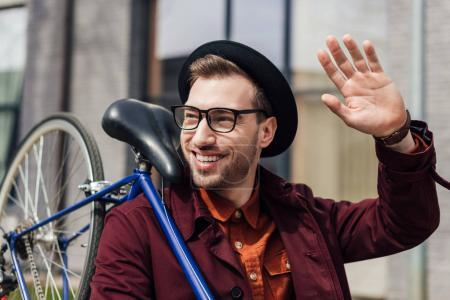 handsome fashionable man waving and carrying bicycle