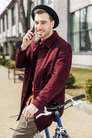 stylish man in eyeglasses and hat talking on smartphone while leaning on bike