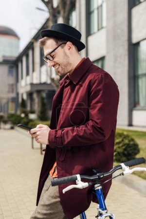 Photo for Handsome stylish man in eyeglasses using smartphone while leaning on bike - Royalty Free Image