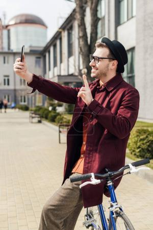 stylish smiling man showing victory sign and taking selfie on smartphone while leaning on bicycle