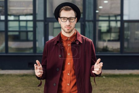 stylish serious man pointing with hand guns gesture