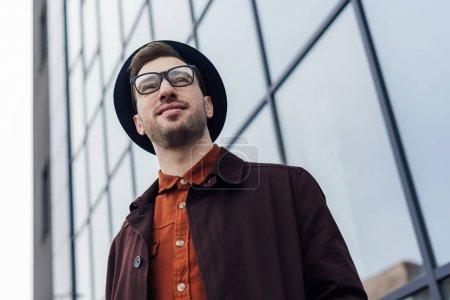 Photo pour Vue de dessous du bel homme élégant posant dans chapeau de verres et de tendance. - image libre de droit