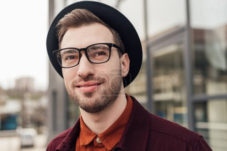 handsome fashionable man in eyeglasses and hat