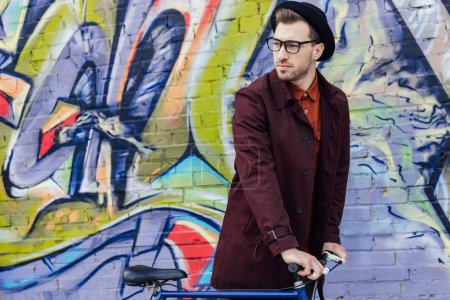 Photo for Stylish man standing with bicycle at wall with graffiti - Royalty Free Image