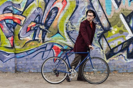 Photo for Stylish elegant man standing with bike at wall with graffiti - Royalty Free Image