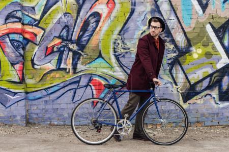 élégant homme élégant debout avec vélo au mur avec graffiti