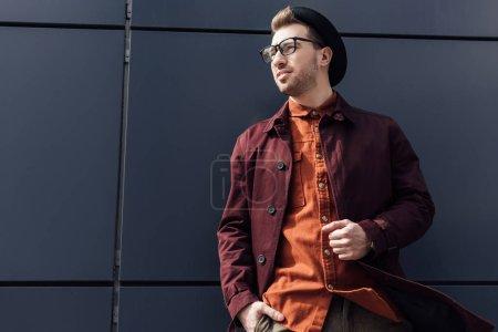 Photo pour Bel homme élégant au mur noir - image libre de droit