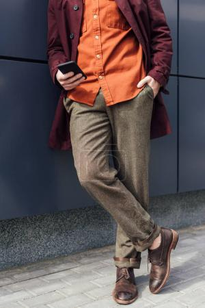 low section view of man in trendy clothes using cellphone