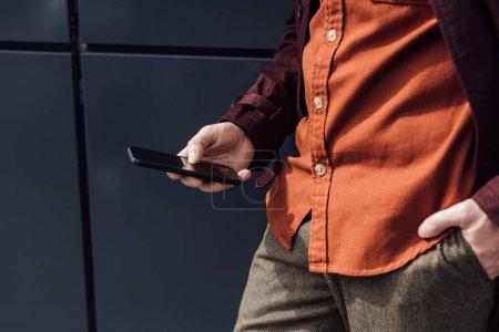 Photo pour Recadrée de l'homme élégant en utilisant le smartphone - image libre de droit