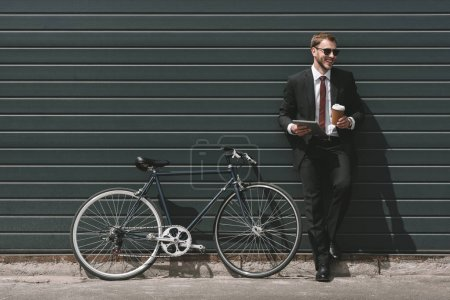 Photo for Stylish businessman with bicycle using digital tablet and drinking coffee while standing in front of black wall - Royalty Free Image