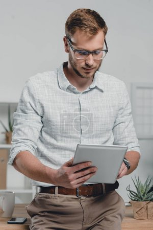 Photo for Focused caucasian businessman using digital tablet and leaning on table in modern office - Royalty Free Image