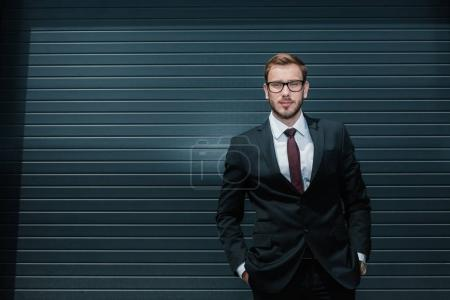 Photo for Confident caucasian businessman wearing suit and eyeglasses, standing and looking at camera - Royalty Free Image