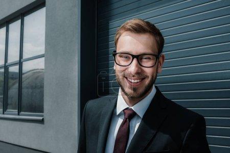 Photo pour Heureux homme d'affaires caucasien portant costume et lunettes tout en regardant la caméra - image libre de droit