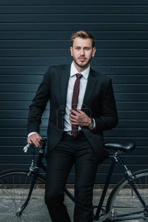 Photo pour Beau jeune homme d'affaires assis sur le vélo et ajuster la cravate - image libre de droit