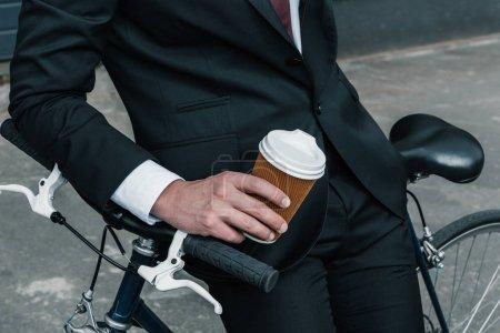 Photo pour Recadrée tir d'homme d'affaires élégant assis sur le vélo et tenant la tasse de café en papier - image libre de droit