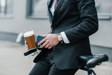 Photo for Cropped shot of stylish businessman holding smartphone and coffee cup while sitting on bicycle - Royalty Free Image