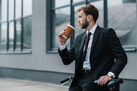Photo for Stylish young businessman sitting on bicycle and drinking coffee - Royalty Free Image