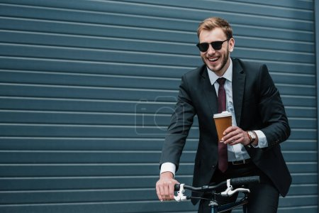 Photo for Smiling young businessman in sunglasses holding paper cup while riding bicycle - Royalty Free Image