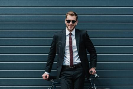 Photo for Stylish businessman in sunglasses sitting on bicycle and smiling at camera - Royalty Free Image