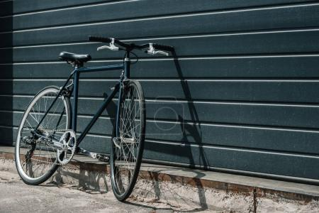 Photo for Black classic hipster bicycle standing near black wall outdoors - Royalty Free Image