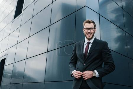 Photo for Handsome stylish young businessman wearing eyeglasses and smiling at camera - Royalty Free Image