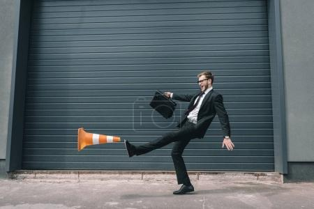 Photo for Excited businessman in eyeglasses holding briefcase and kicking traffic cone - Royalty Free Image