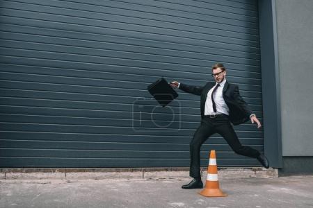 Businessman with traffic cone