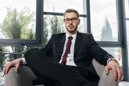 Businessman in suit sitting on armchair at office