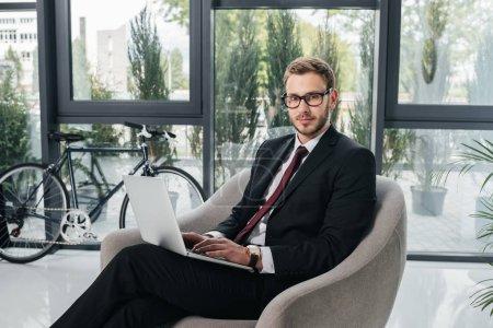Foto de Joven empresario en traje mirando a cámara mientras trabajaba en la computadora portátil en oficina - Imagen libre de derechos