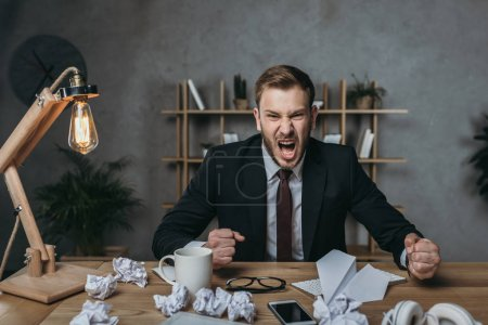 angry businessman yelling while sitting at workplace