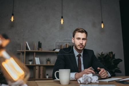young businessman in suit sitting at workplace