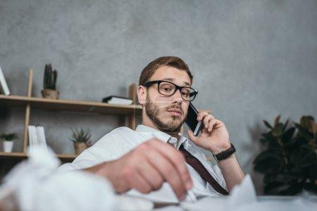Foto de Joven hombre de negocios caucásico hablando en teléfono inteligente mientras está sentado en el lugar de trabajo - Imagen libre de derechos