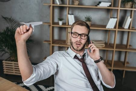 Businessman talking on smartphone while sitting at workplace