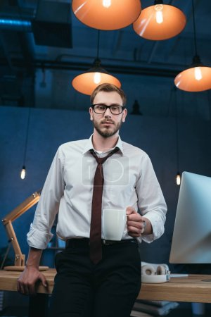 businessman holding coffee cup at office