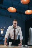 businessman leaning on table at office