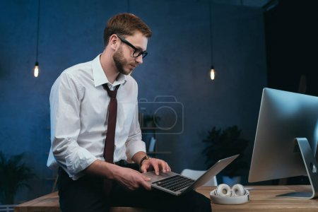 Young businessman working on laptop at office
