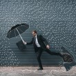Stylish businessman in eyeglasses holding briefcase and running with drawn umbrella