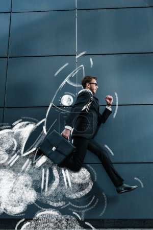 Photo for Side view of stylish businessman with briefcase running and jumping with rocket on back - Royalty Free Image