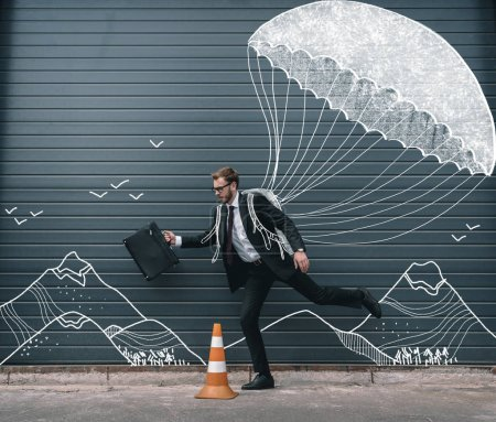 Photo for Stylish businessman in eyeglasses holding briefcase and running with drawn parachute - Royalty Free Image
