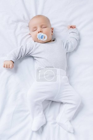 Photo for Overhead view of baby with pacifier in mouth sleeping on bed - Royalty Free Image