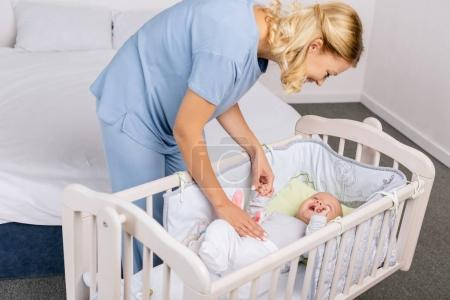 mother looking at baby in crib