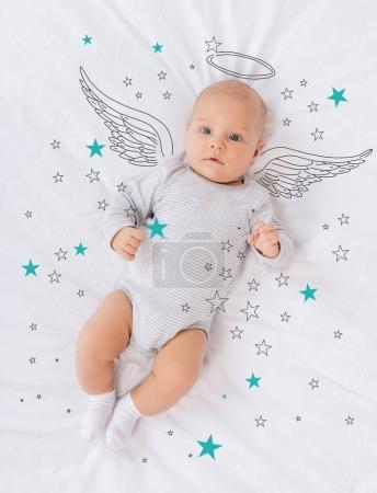 Photo for Overhead view of innocent caucasian baby angel lying on bed - Royalty Free Image