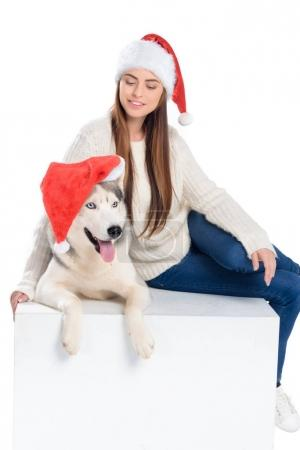 husky dog and beautiful woman in santa hats, isolated on white